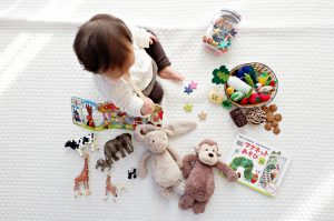 A toddler sitting between variety of toys purchased online