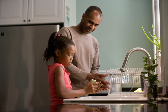 Father making a girl wash her hands