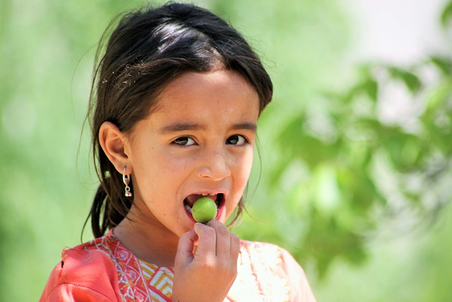 A child eating fruit plucked from tree