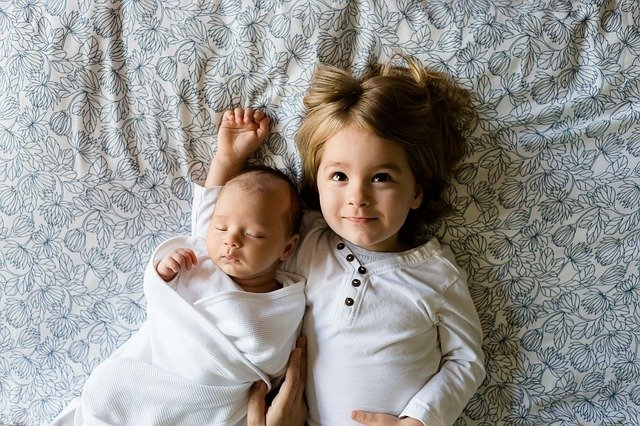 Buy kids wear online - girl lying on bed with little baby brother in soft nightwear