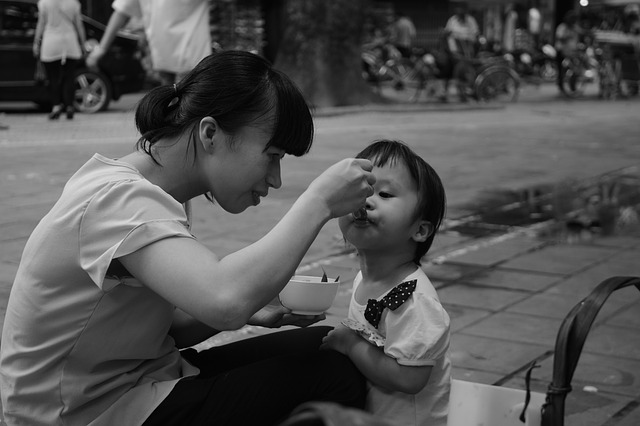 Mother force feeding a baby
