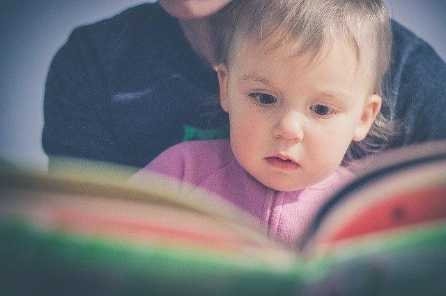 A little baby engrossed in reading a book