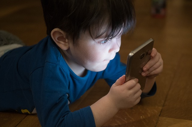 Kid engrossed in playing games on mobile phone